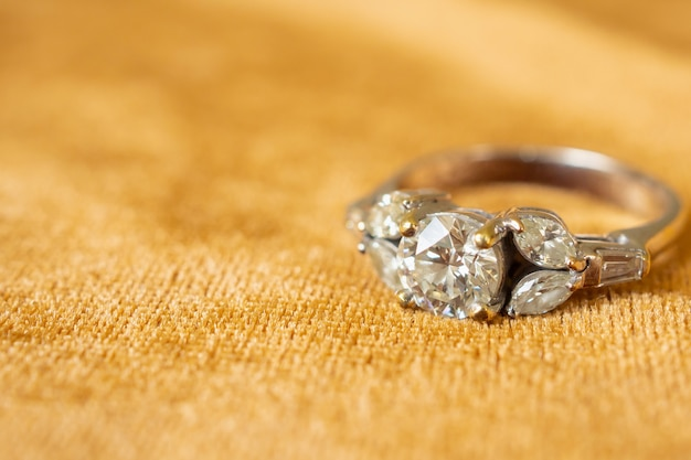Jewelry diamond ring on golden fabric close up