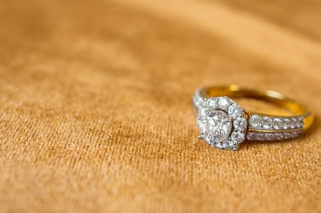 황금 직물 배경에 보석 다이아몬드 반지를 닫습니다.