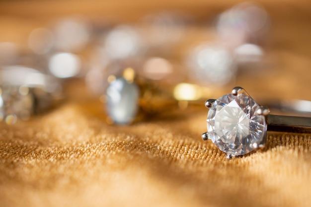황금 직물에 보석 다이아몬드 반지를 닫습니다.