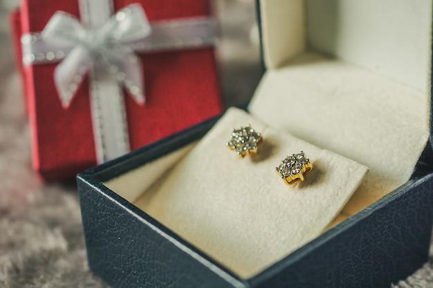 선물 상자 배경으로 보석 골드 다이아몬드 귀걸이