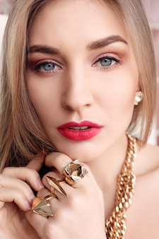ジュエリー、休日、贅沢、そして人々のコンセプト-自然で完璧な肌を持つ美しい女性の顔。ゴールドウーマンスキン。ゴールドのイヤリング、リング、ネックレス。ネイルの化粧品、美容、マニキュア