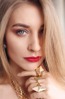 보석, 휴일, 사치 및 사람 개념 - 자연스럽고 완벽한 피부를 가진 아름다운 여성의 얼굴. 골드 우먼 스킨. 금 귀걸이, 반지 및 목걸이입니다. 손톱에 화장품, 미용 및 매니큐어