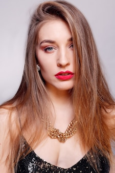 Jewelry, holidays, luxury and people concept - beautiful female face with natural perfect skin. gold woman skin. gold earrings, ring and necklace. cosmetics, beauty and manicure on nails