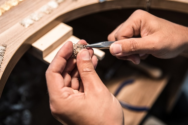 Jewelry maker creating a golden piece