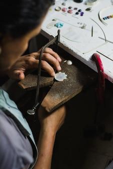 ワークショップで帯鋸で金属を切るジュエリーメーカー。あなたのワークベンチのプロのジュエリージュエラー。