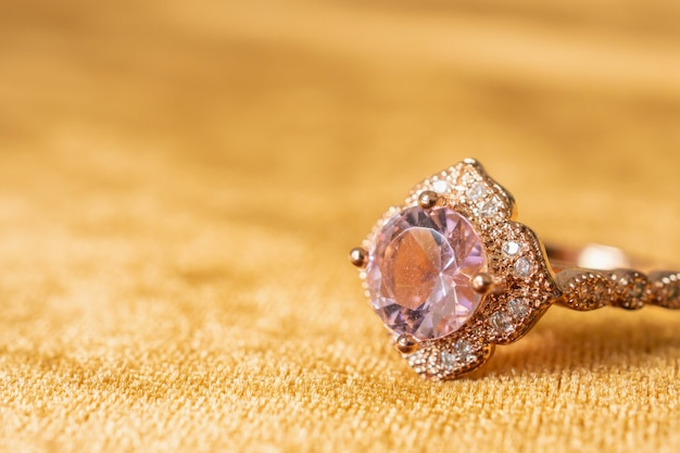Jewelry pink diamond ring on golden fabric background close up