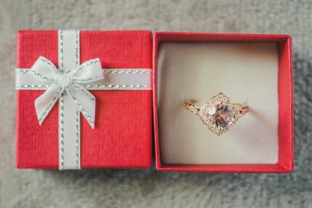 Ювелирное кольцо с розовым бриллиантом в красной подарочной коробке