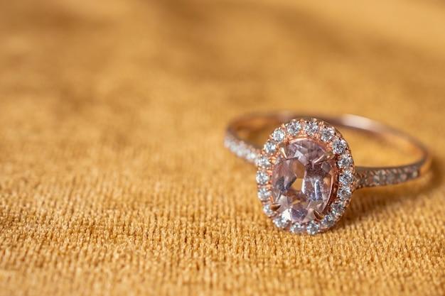 황금 직물 배경에 보석 핑크 다이아몬드 반지를 닫습니다.