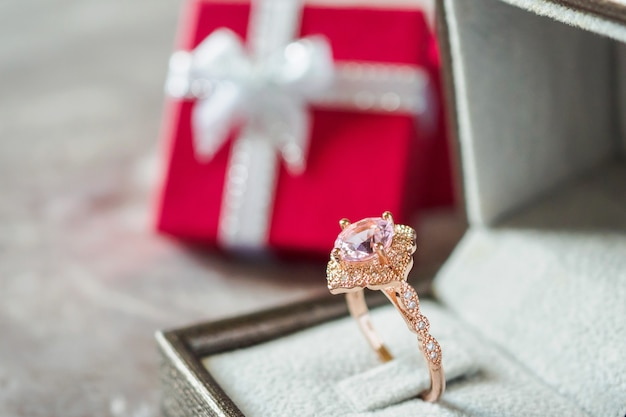 Jewelry pink diamond ring with red gift box background