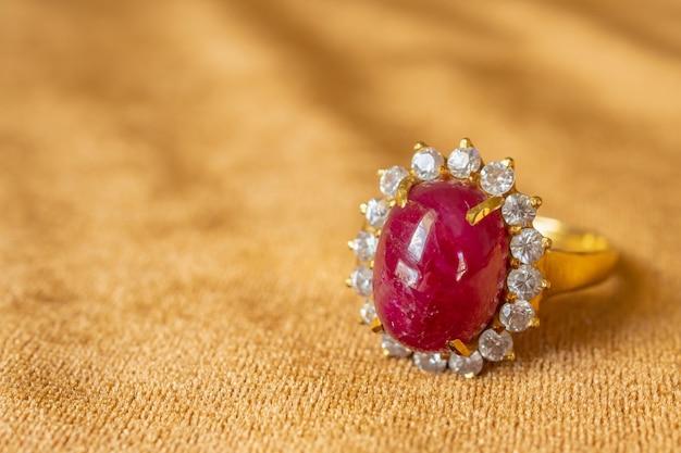 Ювелирное кольцо с красным рубином на фоне золотой ткани крупным планом