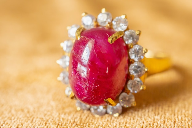 황금 직물에 보석 붉은 루비 반지를 닫습니다.