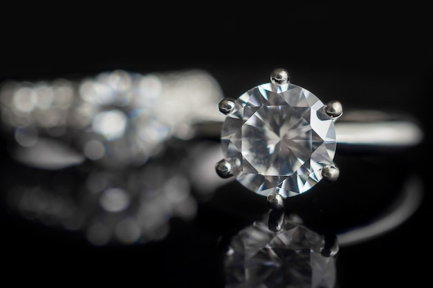 Jewelry wedding diamond rings on black background with reflection