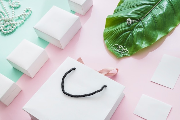 Jewelry with white boxes and leaf on paper backdrop
