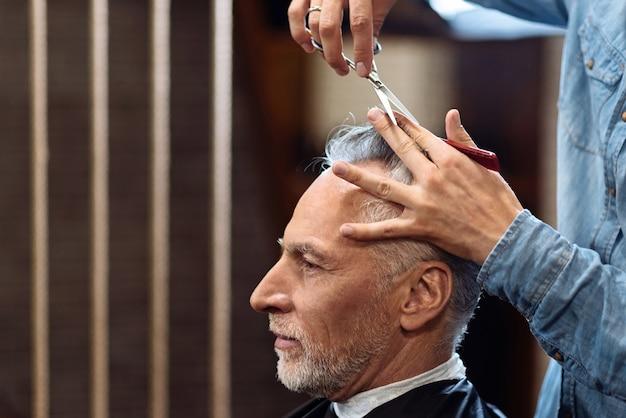 ジュエリーワーク。彼の白髪がプロによってカットされている間、理髪店に座っている快適な年配の男性の側面図。
