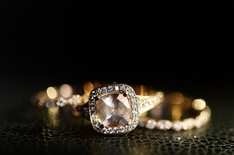 Jewels sparkle in the golden wedding rings lying on the leather