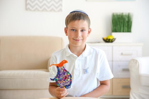 自宅で手作りの水差しを持つユダヤ人の少年