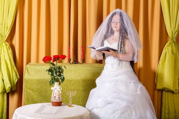 花のあるテーブルで白いドレスのベールに包まれた顔のユダヤ人の花嫁は祈りを読みます