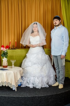 A jewish bride with a veiled badeken face and a groom in a synagogue stand in front of chupa during a ceremony. vertical photo