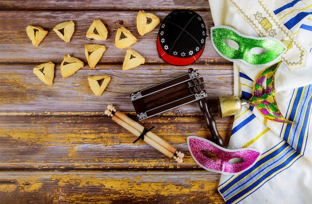 Jewish carnival purim celebration on hamantaschen cookies, noisemaker and mask with parchment