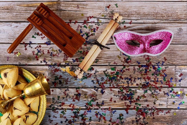 Празднование пурима еврейского карнавала на печенье hamantaschen, шумогенератор и маска с пергаментом вид сверху сверху.