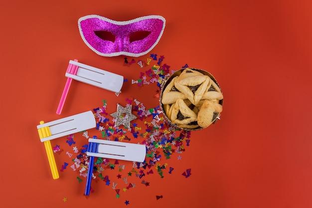 Празднование пурима на еврейском карнавале с печеньем hamantaschen, шумогенератором и маской