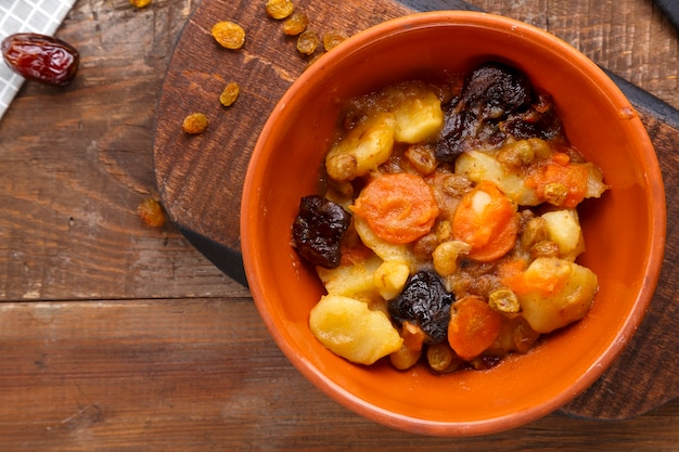 Jewish cuisine dish sweet tsimes with carrot dates in a clay plate on a wooden board