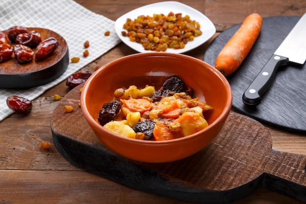 Jewish cuisine dish sweet tsimes with carrot dates vegetarian in a clay plate on a wooden board near candied fruits