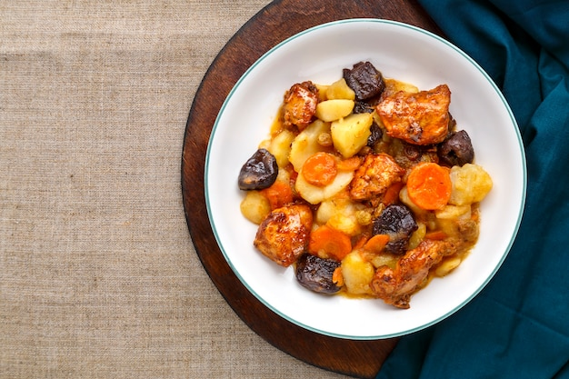 Jewish cuisine dish sweet tsimes with carrots, dates and turkey meat in a white plate on a round board on a linen surface