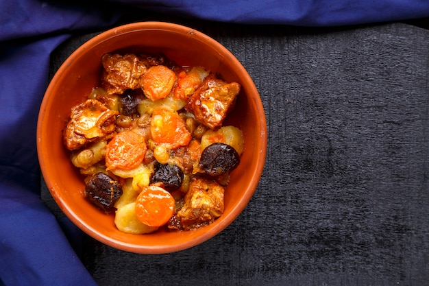 Jewish cuisine dish sweet tsimes with dates, carrots and turkey meat in a brown plate on a blue surface