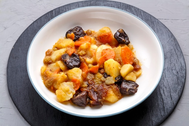 Jewish cuisine dish sweet zimmes with vegetarian dates carrots in a plate on a concrete surface