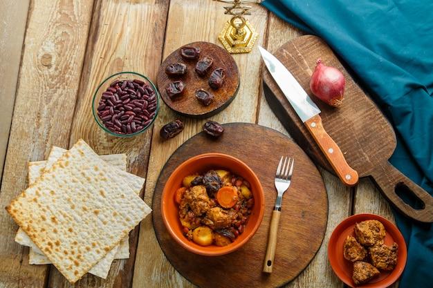 材料の隣のスタンドにある木製のテーブルの上の皿に肉が入ったユダヤ料理のチェルト。横の写真