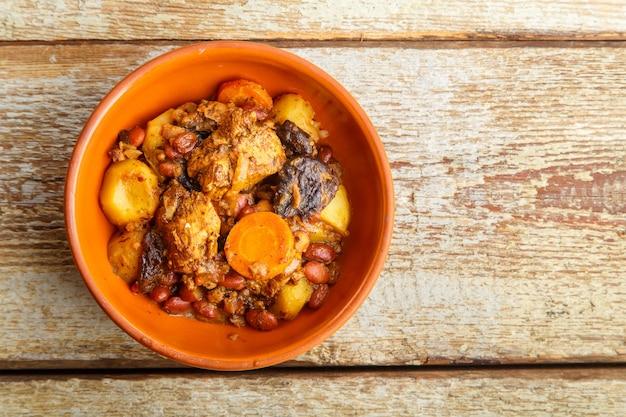 접시에 나무 테이블에 고기와 함께 유대인 요리 chelnt. 복사 공간