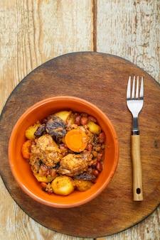 둥근 나무 스탠드에 접시에 테이블에 고기와 유대인 요리 chelnt.