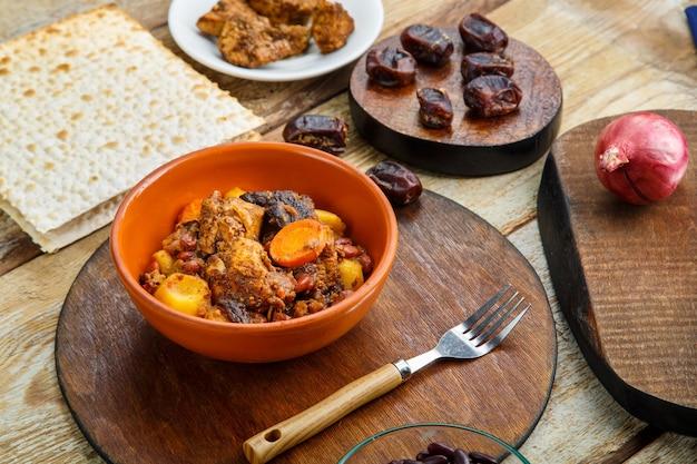 재료와 맛조 옆 스탠드에 있는 접시에 있는 테이블에 고기를 곁들인 유대인 요리.