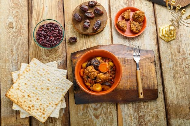 マッツォと食材の近くの木製テーブルにある粘土皿に肉を入れたユダヤ料理のシャトル。横の写真