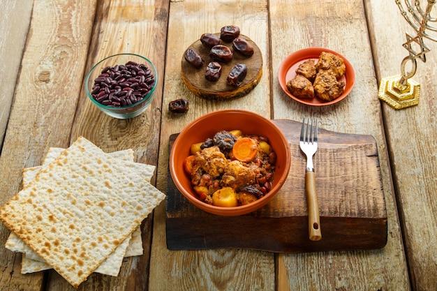 마초와 재료 근처의 나무 테이블에 있는 접시에 고기를 넣은 유대인 요리 셔틀.