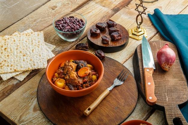 Matzo 옆에 있는 나무 테이블에 있는 접시에 고기를 넣은 유대인 요리 셔틀. 포크와 재료.