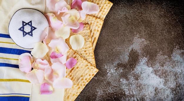 タリットとキッパーで過越祭マッツォユダヤ人種なしパンの休日を祝うユダヤ人の家族