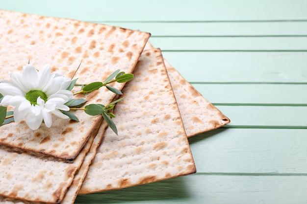 過ぎ越しの祭りと木製の背景、クローズアップの花のためのユダヤ人のフラットブレッドマツァ