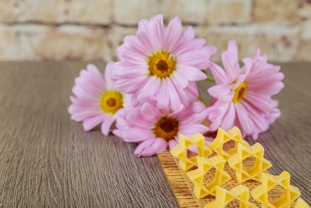 ピンクの花の背景にパスタスープそばのユダヤ教の食べ物ユダヤ教の祝日シンボルパスタ