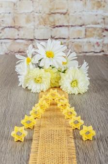 ユダヤ人の食べ物ユダヤ教の祝日シンボルパスタブロスそばパスタ白い花を背景にパスタ