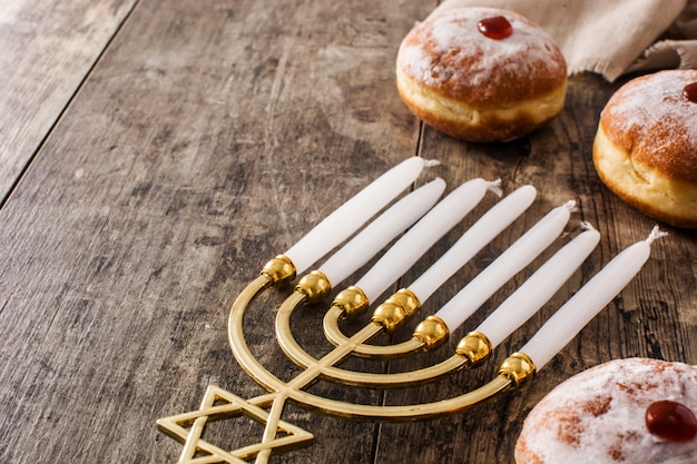 Jewish hanukkah menorah and sufganiyot donuts on blue  copyspace