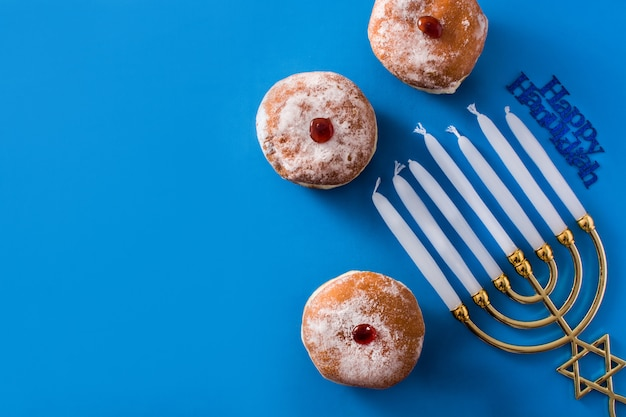 Jewish hanukkah menorah and sufganiyot donuts on blue  top view copyspace