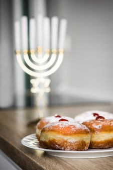 Jewish hanukkah menorah and sufganiyot donuts on wooden table