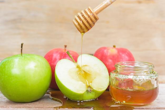 Еврейский праздник яблоко рош ха-шана мед в банке и капля меда на зеленые яблоки