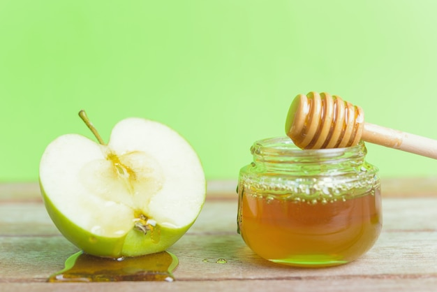 Jewish holiday apple rosh hashanah on the photo have honey in jar and drop honey on green apples