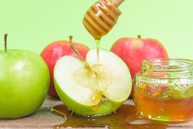 ユダヤ教の祝日アップルロッシュハシャナ写真は瓶に蜂蜜を入れ、青リンゴに蜂蜜を落とします