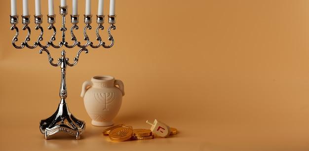 Еврейский праздник хануки фон с монетами меноры и кувшином на персиковом фоне