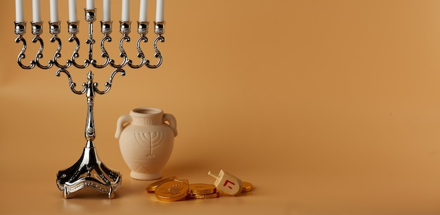 Jewish holiday hanukkah background with menorah spinning topcoins and jug on peach background