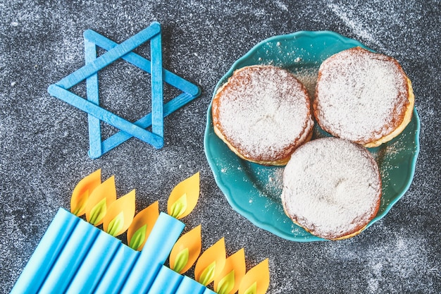 Jewish holiday hanukkah and its attributes, menorah, donuts, star of david. hanukkah menor
